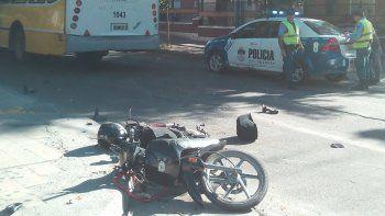 La moto caída y el colectivo del ramal 13 de Indalo, con visibles marcas del choque en su costado derecho.
