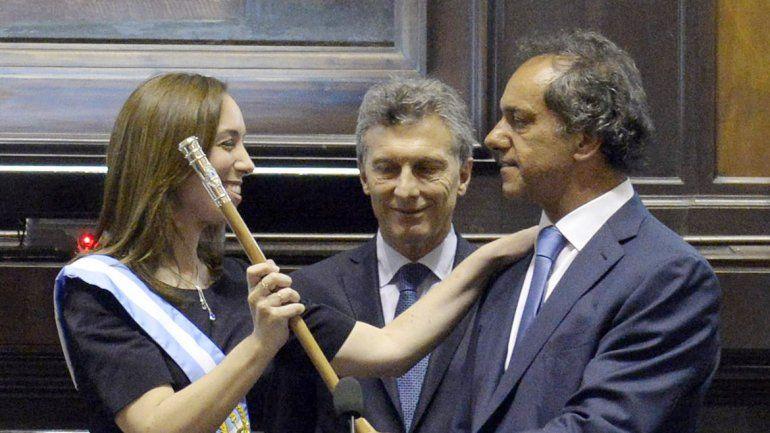 María Eugenia Vidal recibe el bastón de Daniel Scioli. Mauricio Macri mira.