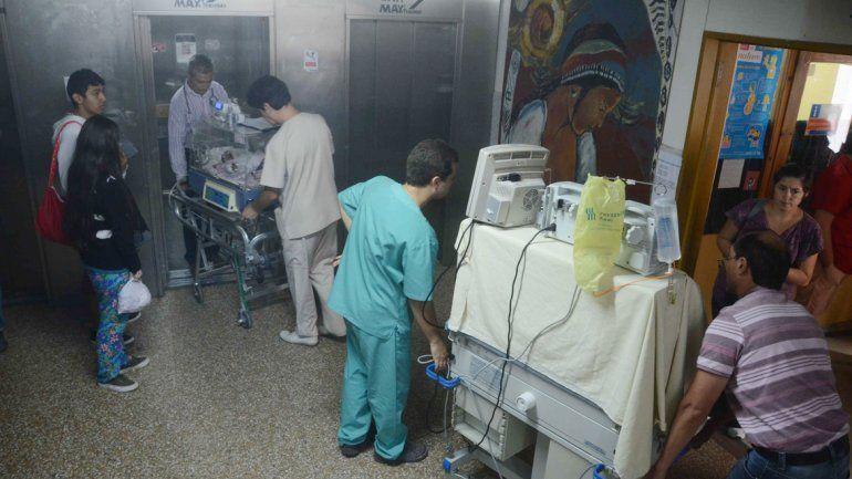 Médicos y enfermeros trasladan a dos bebés prematuros para ser reubicados en otro sector del hospital.