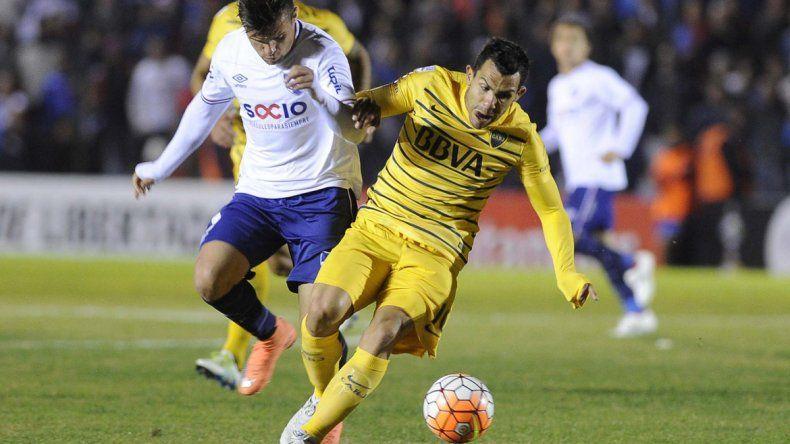 Tevez es seguido de cerca por el defensor uruguayo.