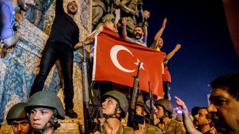 Soldados permanecen con armas en la plaza de Taksim en tanto la gente protesta por el golpe militar.