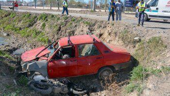 un auto y una moto cayeron a un canal luego de chocar