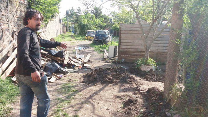 Un hombre señala el lugar donde fue hallado el cadáver.