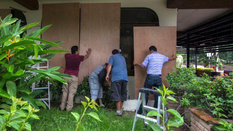 Cuatro hombres colocando protecciones para mitigar el impacto del potente huracán.