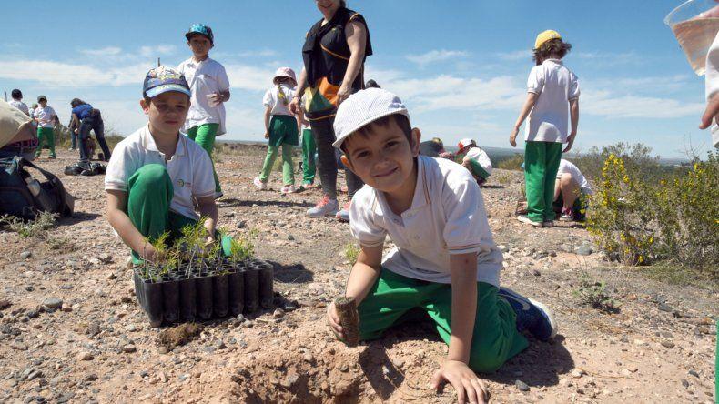 Dos alumnos de los colegios participantes plantaron en Parque Norte.