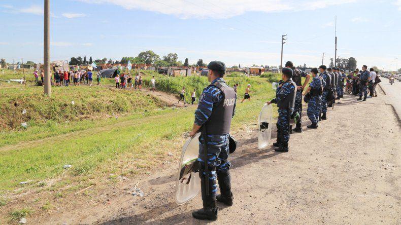 Efectivos de la Policía Bonaerense en los predios que permanecen ocupados. Esperan la orden judicial para actuar.