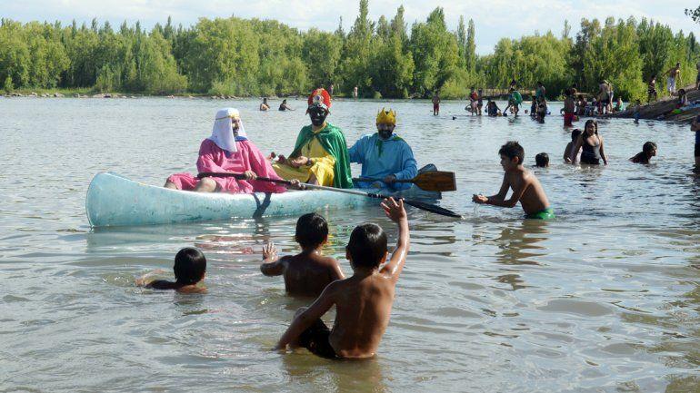 Llegaron en bote y repartieron golosinas. Fueron sensación entre los niños que se bañaban en el Limay.