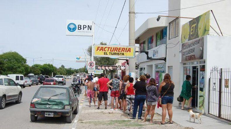 Largas colas frente a una de las sucursales del BPN. La gente se decepciona y se enoja con los comerciantes.