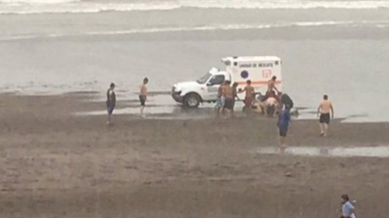 Una ambulancia y los guardavidas en el momento de asistir a un bañista.