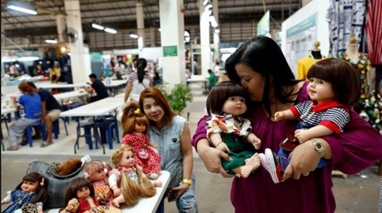 Una mujer tailandesa con sus muñecas espirituales