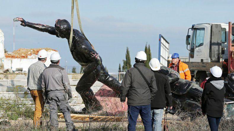 Los operarios sacando una estatua de un dirigente franquista.