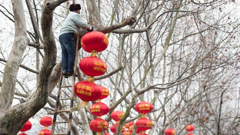 Un operario ornamentando árboles en Pekín en ocasión de Año Nuevo.
