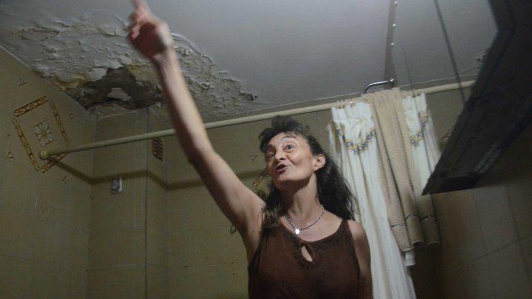 Karina muestra el boquete que le quedó en el techo del baño.