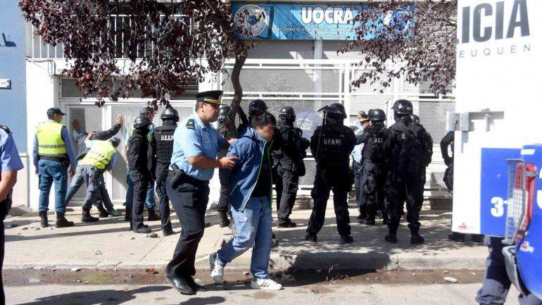 Un policía se lleva detenida a una de las personas que protagonizaron la batalla campal.