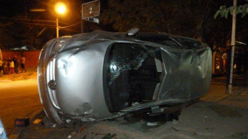 El VW Fox quedó destrozado sobre la vereda después de chocar contra un poste y volcar.