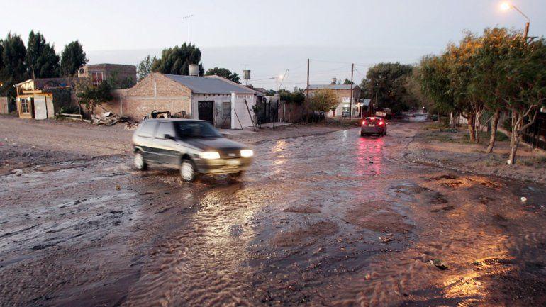 El agua que viene de la cisterna corre por las calles del barrio.