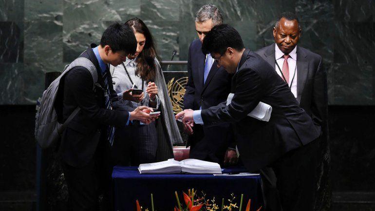 Diplomáticos sacan fotos al texto del acuerdo suscripto ayer.