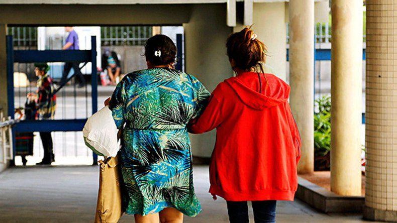 La joven violada saliendo del hospital junto a su madre. La policía difundió fotos de los sospechosos.