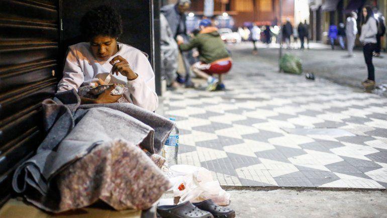 Una mujer comiendo en una calle céntrica de San Pablo