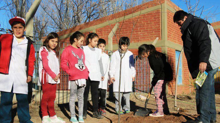 Los chicos plantaron árboles en una escuela del barrio Melipal.