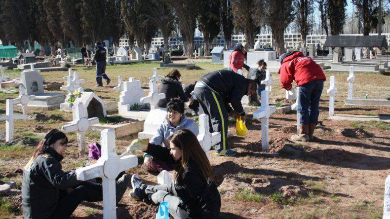 Empleados municipales pintan las cruces del cementerio.