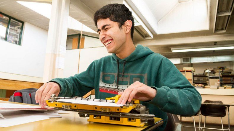 Carlos Tapia y su vieja máquina Perkins con la que estudia. También tiene una computadora parlante.