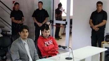 Alejandro Caro, de buzo rojo, y su defensor escuchan el acuerdo.