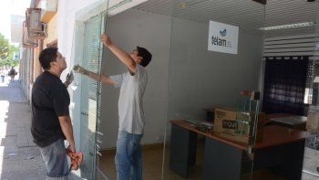 Un obrero cambia el blindex que fue destruido por los delincuentes.