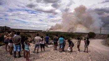 Curiosos miran la columna de fuego en Nueva España mientras los bomberos combaten el fuego.