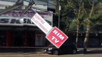 el viento tiro un cartel sobre un auto en el bajo