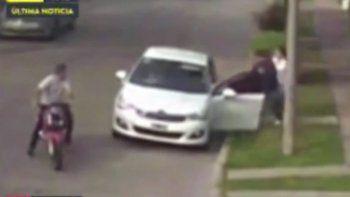 El instante del asalto: el ladrón aborda el auto. En la moto, su cómplice.