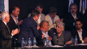 Tapia es saludado por sus laderos Daniel Angelici (Boca) y Hugo Moyano (Independiente).