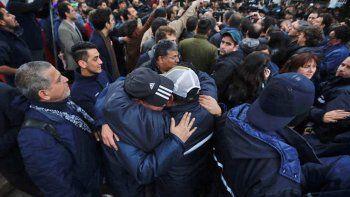 Dos trabajadores de Pepsico se abrazan tras el violento desalojo.