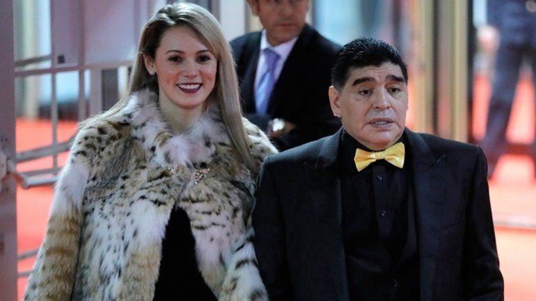 Rocío Oliva acompañó a Maradona al sorteo del Mundial y fue destrozada en las redes por lucir un tapadode piel. El Diez sorprendió con un moño amarillo.
