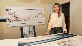 Patricia Gómez en su taller de Centenario. Despliega el arte sumi-e, una técnica de pintura oriental con la que ganó premios internacionales.
