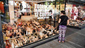 Una mujer mira zapatos en una vidriera de la ciudad. Hubo todo tipo de promociones para la Navidad.