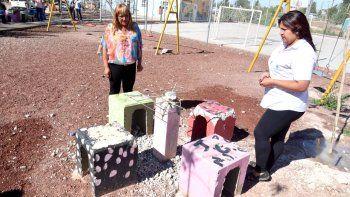 Dos trabajadoras del lugar miran asombradas el estado en que quedó una mesa de hormigón.