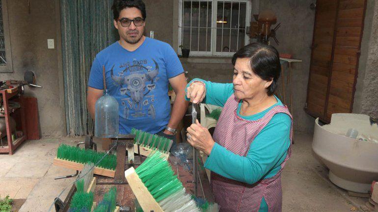 Lucas y Andrés Silosa, junto a su madre María Cristina, exhiben con orgullo sus escobas ecológicas. Trabajan en la casa y venden por Facebook.