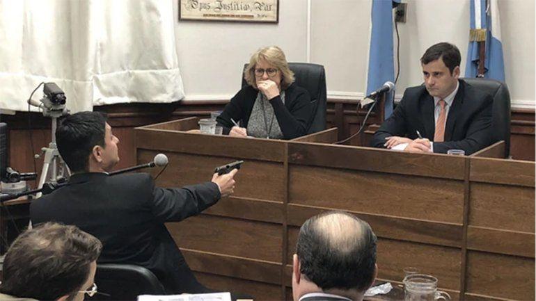<p>Azcué sostiene el arma ante el presidente del tribunal.</p>