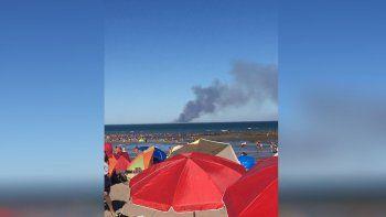 turistas sorprendidos en la playa por una gran columna de humo