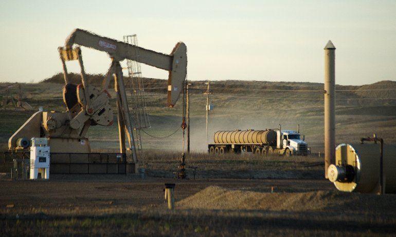 Foto de archivo. Un camión de servicio pasa frente a un pozo y una bomba de petróleo en la Reserva Indígena Fort Berthold en Dakota del Norte