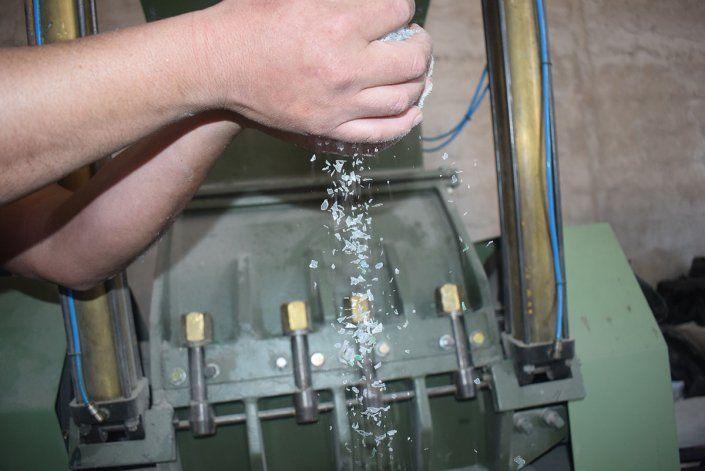 La máquina muele los envases hasta convertirlos en innumerables escamas.