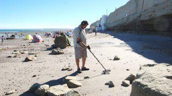 un turista busca tesoros con un detector de metales