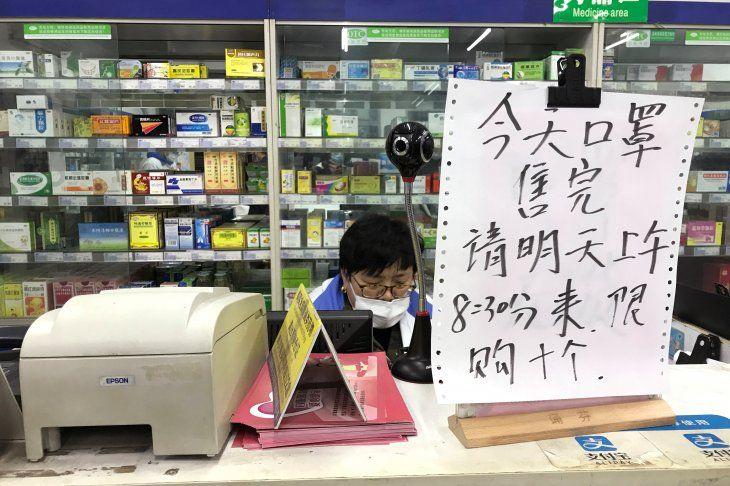 Foto del miércoles del empleado de una farmacia en Shanghái junto a un cartel que indica un límite de venta de 10 máscaras por personas. Ene 29