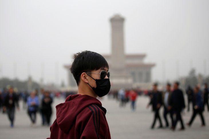 Imagen de archivo de un hombre utilizando una máscara durante una visita a la Plaza Tiananmen en medio de una tormenta de arena en Pekín