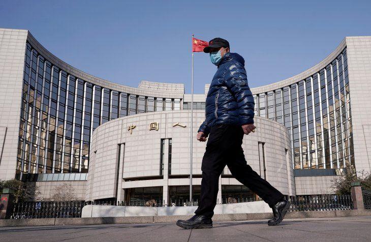 FOTO DE ARCHIVO. Un hombre con una mascarilla camina frente a la sede del Banco Popular de China