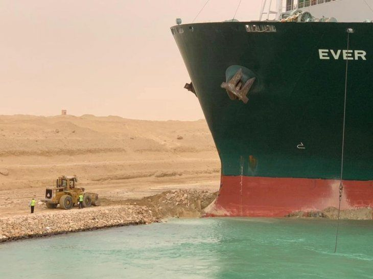 Trabajadores junto a un buque portacontenedores que fue golpeado por un fuerte viento y encalló en el Canal de Suez