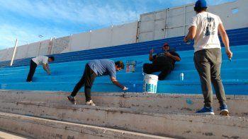 Los hinchas pintando una de las tribunas.