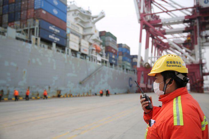 FOTO DE ARCHIVO. Un capataz con una mascarilla trabaja mientras un buque de carga atraca en una terminal de contenedores del puerto de Qingdao