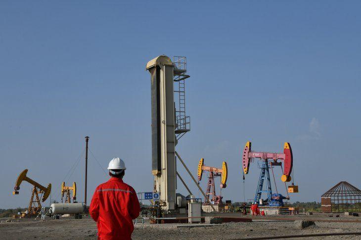 FOTO DE ARCHIVO. Empleados trabajan cerca de bombas de bombeo en un campo petrolífero de China National Petroleum Corp (CNPC) en Bayingol